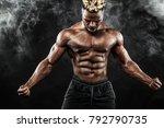 Small photo of Sports wallpaper on dark background. Power athletic guy bodybuilder.