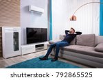 young man relaxing on sofa near ... | Shutterstock . vector #792865525