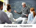 Small photo of Friendly teacher talking to his students at lesson of algebra or trigonometry