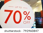 Small photo of Large Sale 70% off letters on a glass wall obstruct a view inside the popular fashion store