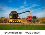 Corn harvester  in the field of buckwheat loading truck in farmland.