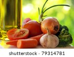 Olive oil and vegetables in green background. - stock photo