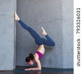 Small photo of Slim female yogi wearing sportswear performing inversion or arm balance standing upside down on forearms