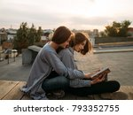 couple sits on a roof top... | Shutterstock . vector #793352755