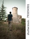 Small photo of Man observing an old fortress in front of him, as a sort of defiance. Italian Castle, placed in Emilia Romagna region.