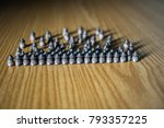 Small photo of lots of airgun dangerous bullets kept on a wooden table and dramatic shadows