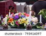 Candles And Flowers On Grave