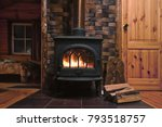 Fragment of the interior of a country house. The iron furnace is heated. There is wood near the stove. It
