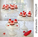 Small photo of Rev velvet cupcakes decorated with red roses and hearts on 3 tier cakestand.