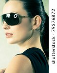 beautiful head shot of brunette with sunglasses photographed in studio. - stock photo