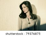 beautiful brunette photographed against yellow wall in afternoon sun light - stock photo