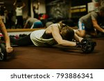 Small photo of Cross fitness wheel Ab Roller workout. Group abs training workout