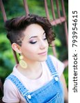 Small photo of Portrait of a young beautiful girl with a stylish hairstyle. Stylish earrings in the ears