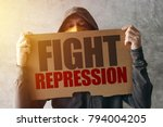 Small photo of Hooded activist protestor holding Fight repression protest sign. Man with hoodie and scarf over face taking part in activism and fighting for the cause.