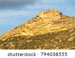 Small photo of Geological formation closeup consisting in a cracked limestone rock outcropping strata at the top of an arid mountain with the warm colors of sunset in Cervera de Rio Alhama, La Rioja, Spain.