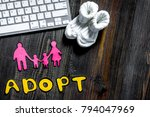 Small photo of Adopt word, paper silhouette of family and booties near keyboard