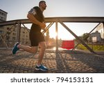 young sporty man jogging across ... | Shutterstock . vector #794153131