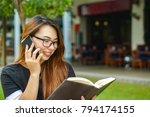 a girl in a park holding a book | Shutterstock . vector #794174155