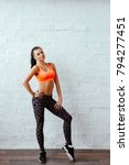 Small photo of sport and yoga lifestyle concept. Young fit pretty woman dressed in sport clothes poses against white brick wall. Portrait to the utmost.