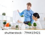 Small photo of Checking schemes. Positive young experienced engineer sitting at their comfortable working place and smiling while looking at the detailed large scheme