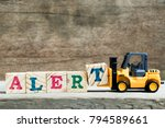 Small photo of Yellow toy forklift hold letter block T to complete word alert on wood background