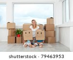 Woman with playing kids in their new home having fun among cardboard boxes - stock photo