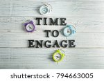 Small photo of Clocks and phrase TIME TO ENGAGE on wooden background