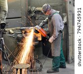 Small photo of Workers in a foundry grind castings with a grinding machine - Heavy industry workplace