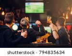 Stock photo three men watches football on tv in a sport bar 794835634