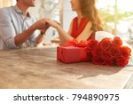 Stock photo cheerful young couple sitting at wooden table of outdoor cafe and holding hands while celebrating 794890975