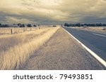 outback fields and road with wind in dry grass - stock photo