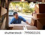 couple unloading boxes from van ...   Shutterstock . vector #795002131