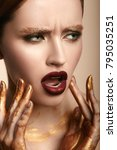 Small photo of Fashion Brunette Woman face creative portrait. Young Beauty Model Girl with gold make-up and gold paint on her fingers touching her face. Female portrait with snuffy expression.