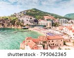 Small photo of Fragment of the old town of Budva: ancient walls and a red tiled roof and a view of a modern beach, Montenegro, Europe. Budva is one of the best and most popular resorts of the Adriatic Riviera.
