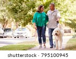 Stock photo senior couple walking dog along suburban street 795100945