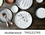Small photo of Ceramic tableware and cutlery on wooden background, top view