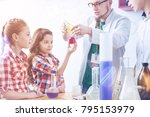 Small photo of Need your help. Adorable future scientists helping their tutor and holding a glass jar full of pink liquid while their teacher strewing chemical powder into it during an experiment.
