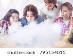 Small photo of Magic is happening. Smart up and coming chemists blowing on the fume appearing after mixing several chemistry liquids together during a scientific research at school.