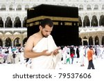 Muslim pilgrims in white traditional clothes, praying at Kaaba in Makkah - stock photo