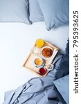 Small photo of Breakfast Bed Wooden Tray Coffee Bun Grey Linens Bedding Sheet Pillow Coverlet Hotel Room Early Morning at Hotel Background Concept Interior Copy Space