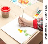 Small photo of A girl draws a drawing with paints on a sheet