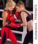 Small photo of Two boxing women workout in fitness class. Sport exercise two female people. Boxer wearing red gloves to box in ring. Cruel competitions.