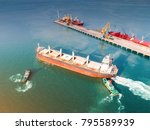 Small photo of general bulk cargo ship under navigating by pilot leader takes the ship sailing safety circumstance from the wharf terminal seaport assist by tugs boat serving