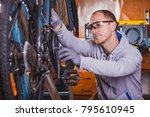 handsome bicycle mechanic doing ... | Shutterstock . vector #795610945