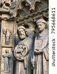 Small photo of Notre Dame de Paris Cathedral. Architectural details. Catholic saints statues. Sheep as symbol of caring for devotees and narrow-toed crayfish (resident of French rivers) as warning against apostasy