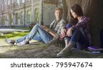 Stock photo two young people sitting under tree girl looking down and guy looking at her 795947674