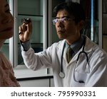 Small photo of Asian doctor examining a patient's ear canal. Low key dark medical consulting office backgound. Doctors' day and health care concept