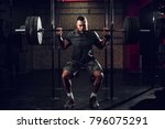 Small photo of Strong motivated and focused muscular bearded short hair bodybuilder man holding a heavyweight barbell on the shoulder behind the neck while crouching and doing squats exercise in the dark gym.