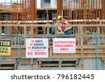 Small photo of Workers adhere to rules and regulations posted on the construction site.
