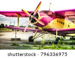 Small photo of Abstract, old yellow, pink, purple plane in abandoned airport next to dark forest in an overcast day. Military plane, russian aircraft. Soviet mass-produced single-engine biplane at field aerodrome.